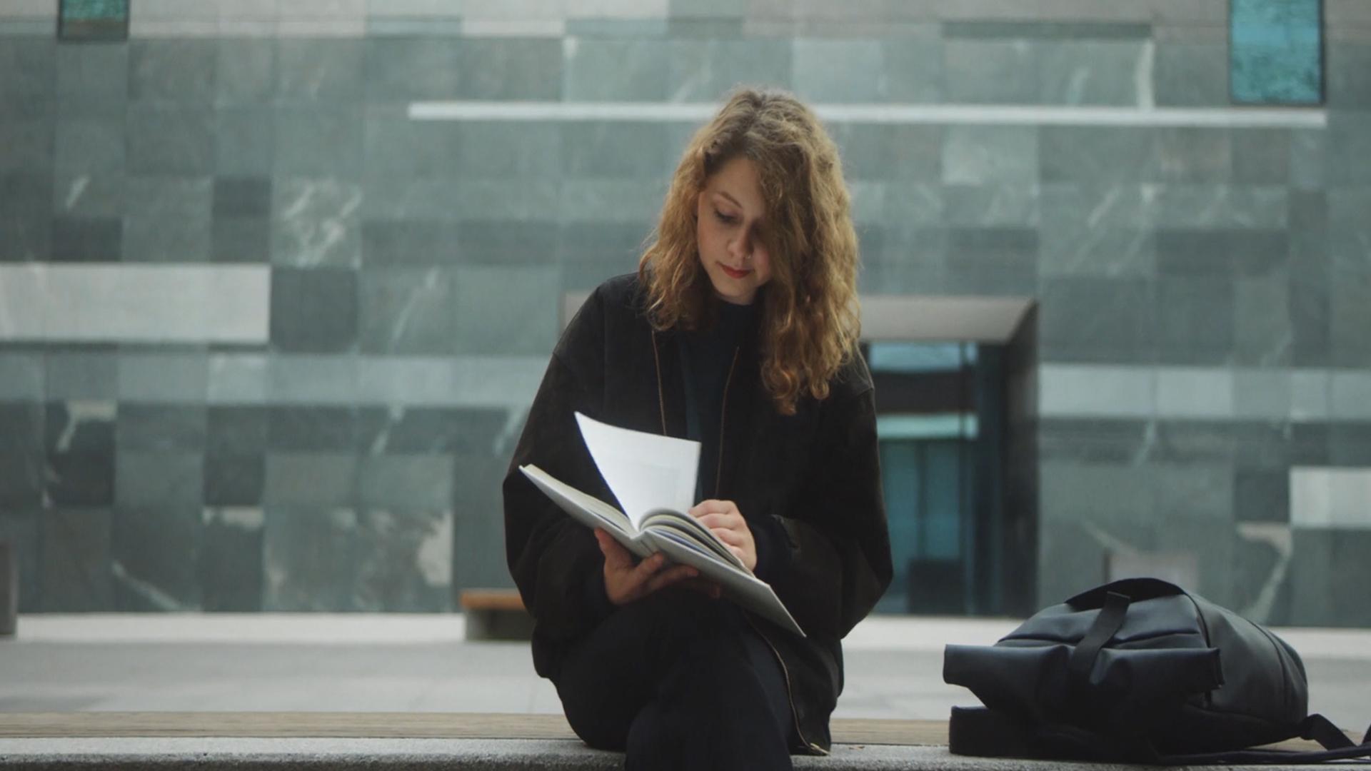 Filmproduktion Imagefilm Universität Leipzig Stadt Frau liest Buch auf Campus